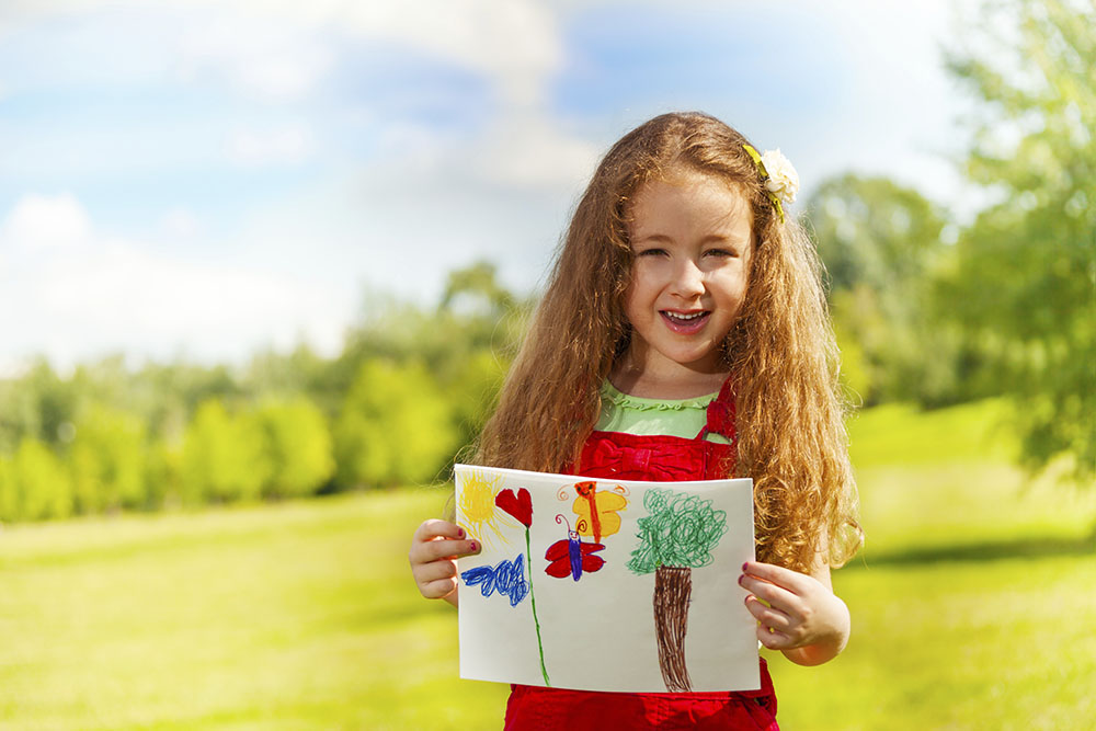 Closeup portrait of beautiful 6 years old girl standing in the park with painted image on summer day